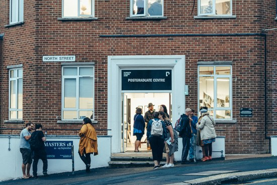 Students outside the open door of Plymouth College of Art Postgraduate Centre