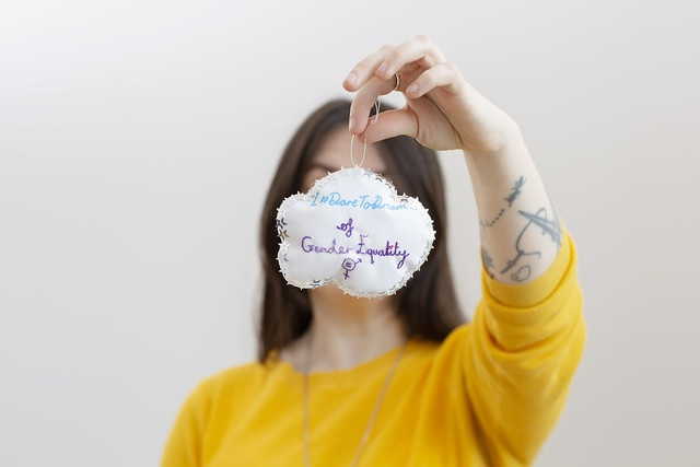 I dare to dream of gender equality is stitched into a fabric cloud. Sarah Corbett is holding the cloud in front of her face