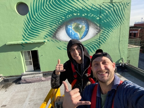 two men on a roof with the mural of a green eye behind them