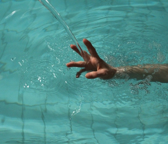 a stream of water is falling on a hand in a pool