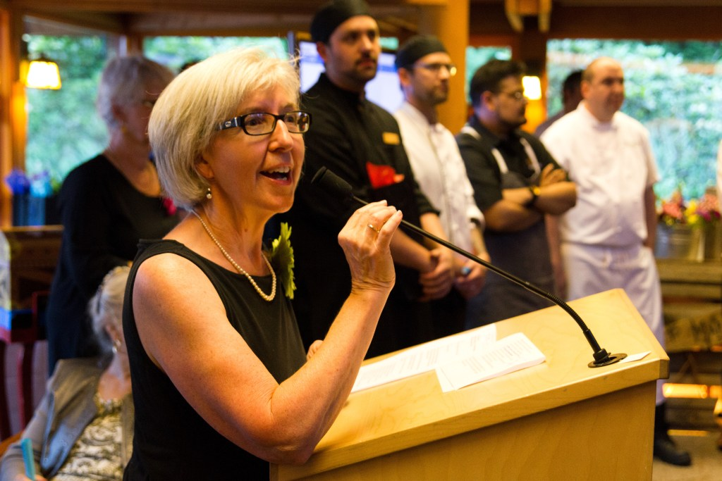 Colour Your Palate organizing committee chair, Maureen Weston, speaks at the microphone while chefs stand behind her.