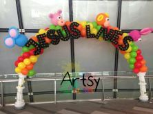 """Rainbow balloon arch with columns at the side and """"JESUS LIVES"""" advance balloon alphabets"""