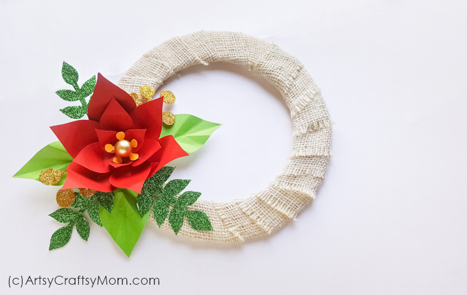 Make this Paper Poinsettia Wreath Craft to pretty up your front door this holiday season - with a little bit of rustic flavor and a little bit of glitter!