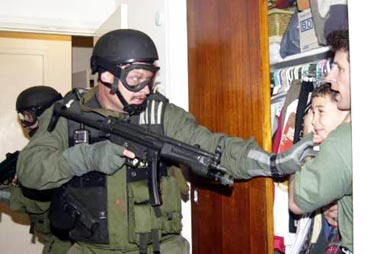 In this fourth of seven sequential photos, fisherman Donato Dalrymple holds 6-year-old Elian Gonzalez inside a bedroom closet Saturday, April 22, 2000, as a Border Patrol agent puts his arm out to the boy moments after federal agents raided the Miami home. (AP Photo/Alan Diaz)