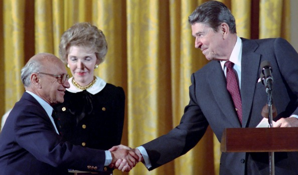 Milton Friedman shaking hands with Ronald Reagan while Nancy Reagan looks on.