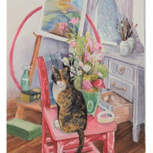 Tortoise shell calico cat on red chair in artist's studio.