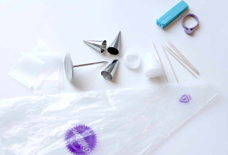 piping bags, wax paper squares, flower nail, #1.5, #2, & #101 tips, coupler and ring, toothpicks, and bag closures