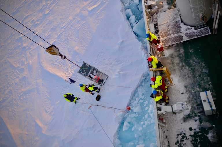 Attaching the sediment traps to an ice floe: Martí, Yasemin and Jørn as a polar bear guard are lifted onto the ice to secure the traps. Photo: Èric Jordà Molina (Nord Univ.).