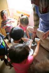 Waldorf Nursery students washing dishes with their teacher.