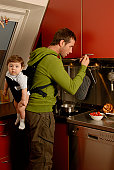 Father carrying baby son (7-9 months) on back while cooking in kitchen