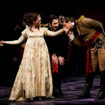 Iago looks on as Desdemona and Cassio exchange pleasantries