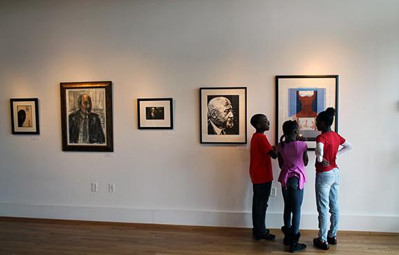 Three students looking at art