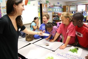anthropology student talks to students about insects
