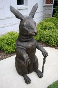 Bronze sculpture of a rabbit holding a cane