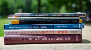 stack of books written by faculty and one alumnus