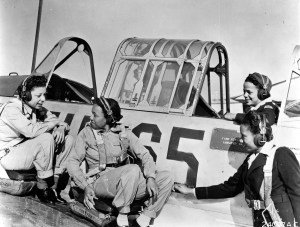 A black and white photo of the Tuskegee Airwomen with a plane.