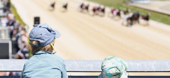 Dos niños ven carreras de caballos en sillas de montar en Addington Raceway (Nueva Zelanda).