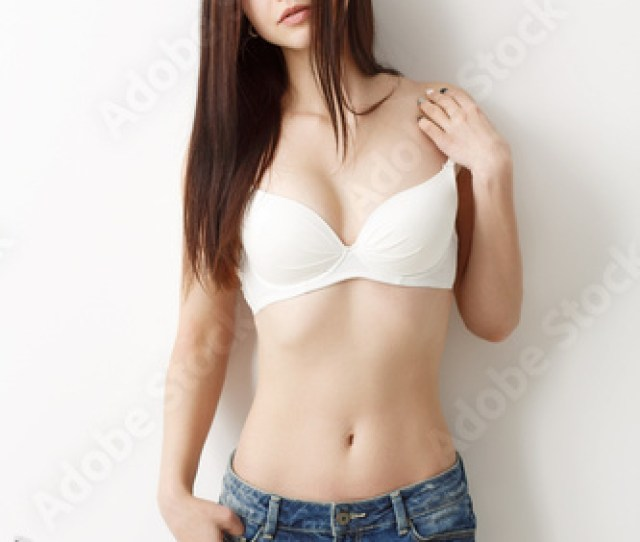 Emotional Portrait Of A Young Sexy Girl In Shorts And A Bra On A White Wall Background