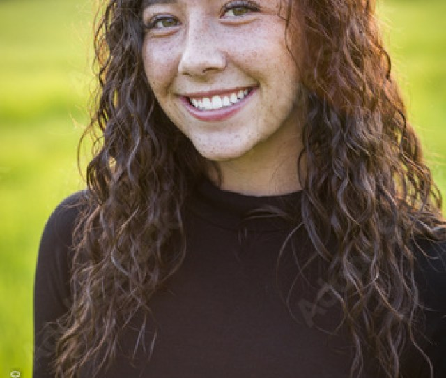 A Beautiful Hispanic Teen Girl Outdoor Portrait Cute And Smiling Woman With Brown Hair Looking At The Camera Standing In A Scenic Field Outdoors