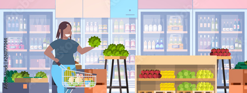 fat obese woman with shopping trolley cart choosing groceries ...