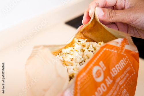 opening a microwave popcorn bag stock