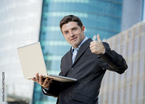 businessman holding computer laptop working urban business outdoors