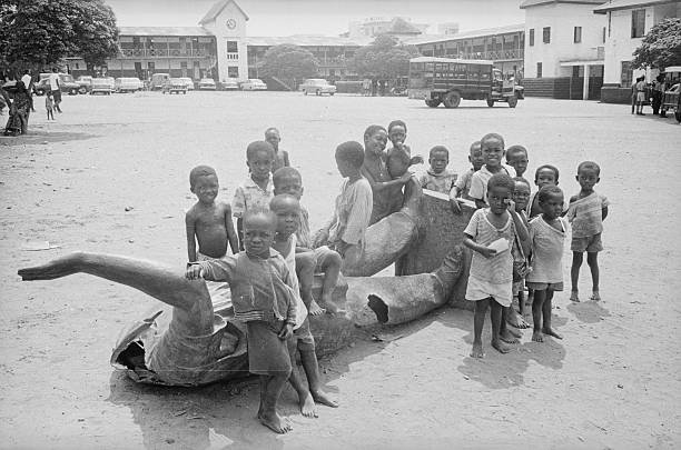 Children with toppled statue of Kwame Nkrumah