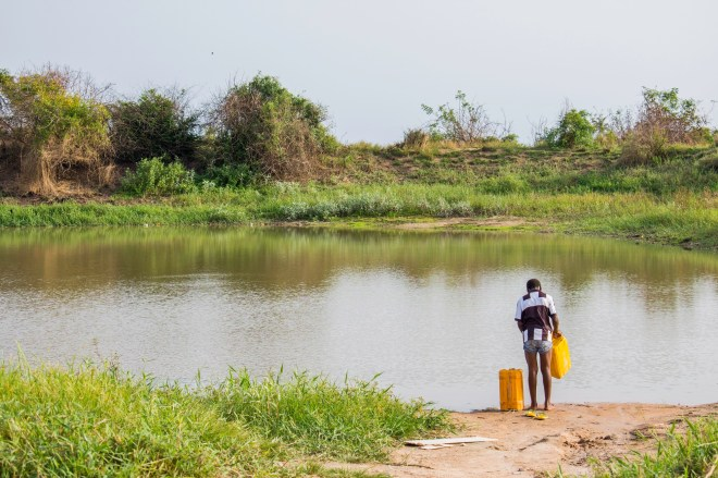boy about to walk into the pond to fetch water
