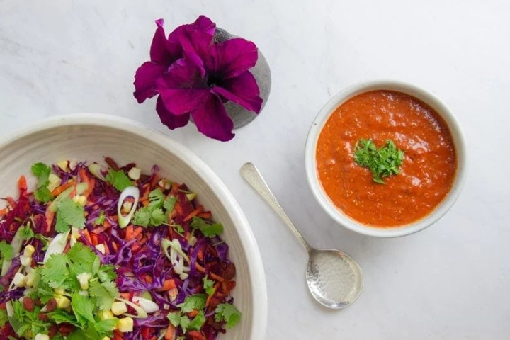 Colourful raw salad with a bowl of bright orange dressing next to it