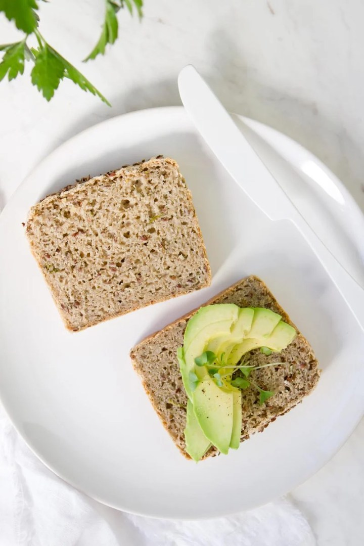 Two slices of spongy homemade bread on a white plate, with a few slices of avocado on one piece