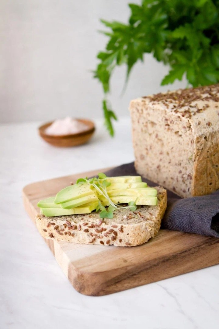 Baked loaf of bread, sliced and topped with avocado, on a wooden board