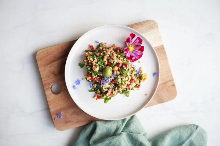 A single serving of colourful Moroccan sorghum salad on a plate with a pink flower