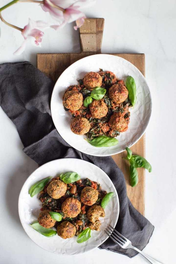 Two dinner plates filled with lentil meatballs, marinara sauce and greens, on a large wooden chopping board