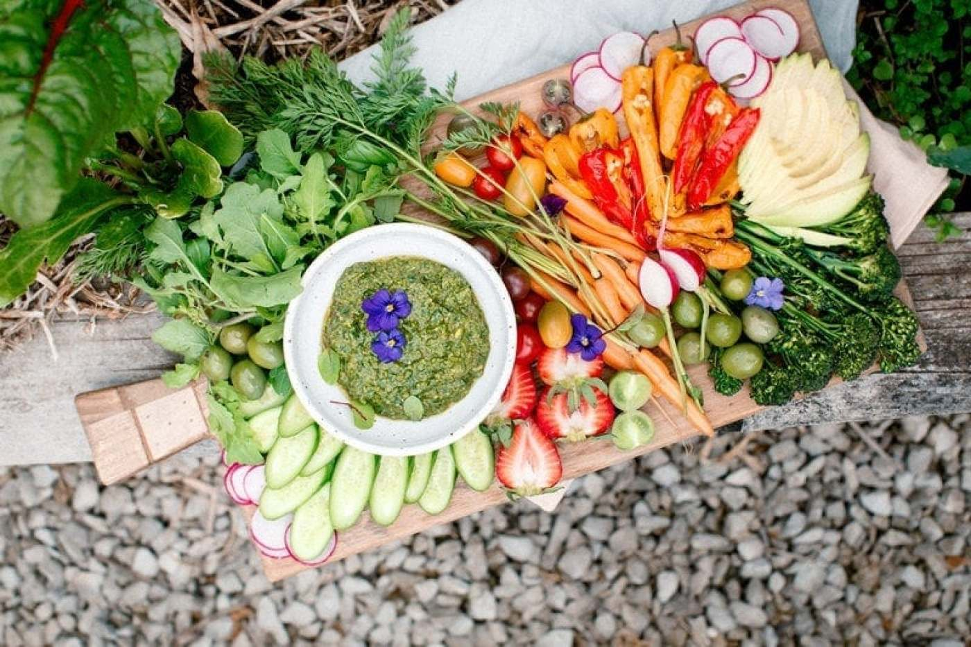 Wide shot of rustic board crammed with fresh vegetables and pesto resting on garden bed