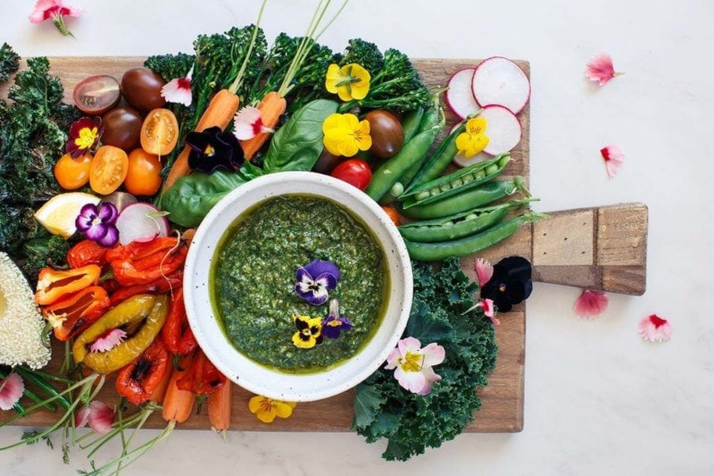 Rustic chopping board filled with coloured raw vegetables and a bowl of green, vegan basil pesto