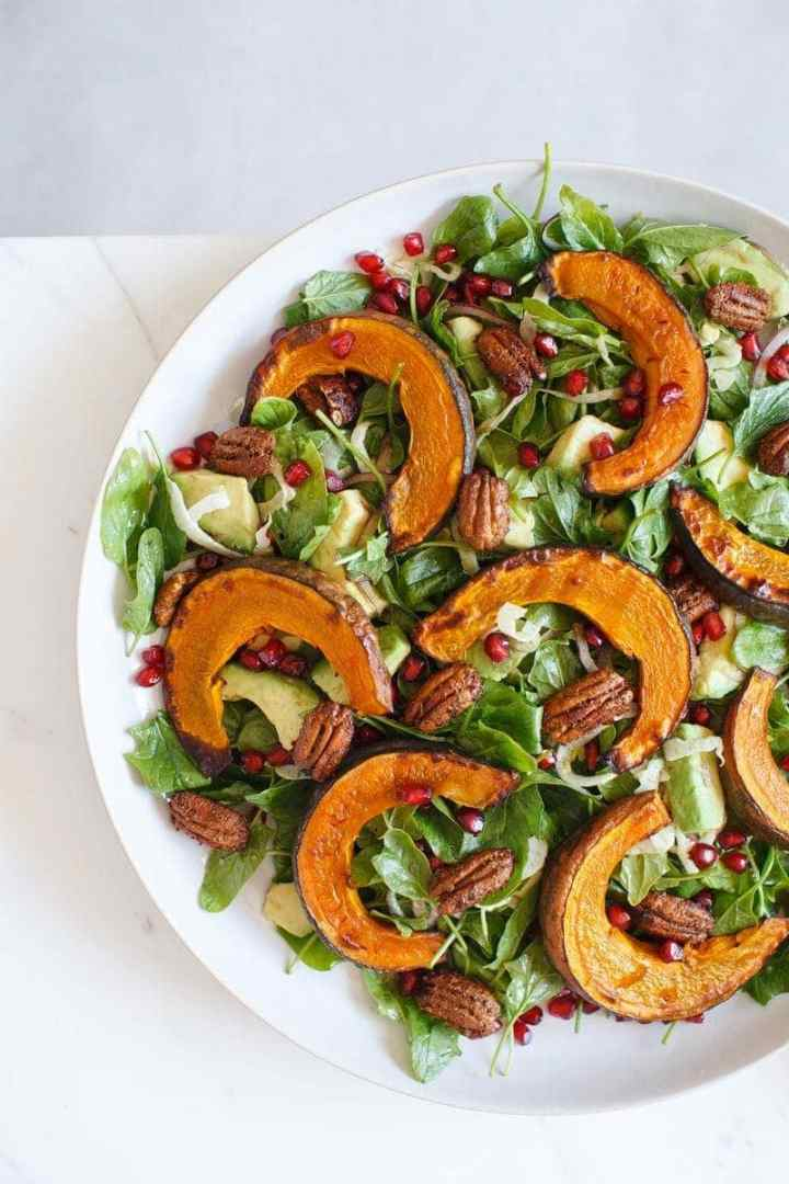 Squash salad with pomegranate and avocado arranged beautifully on a white plate