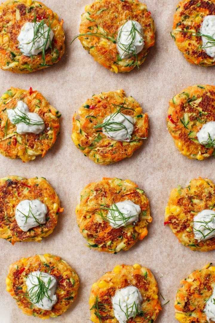 Close up of a dozen bite-sized vegetable fritters on a chopping board garnished and ready to serve