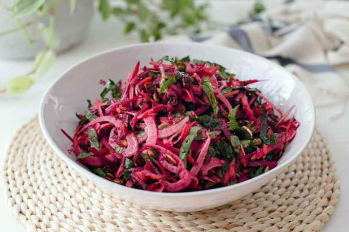 Close up of a bowl of colourful raw beetroot salad in a white bowl on a woven placemat
