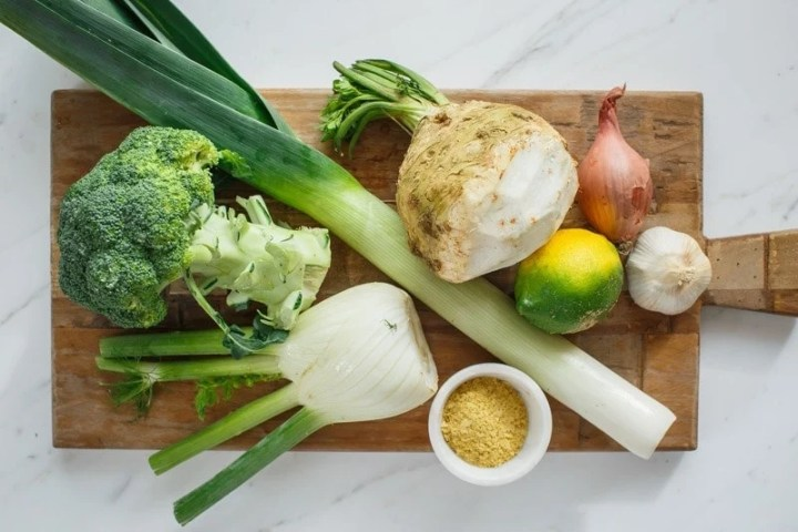 Ingredients for celeriac soup laid out on a wooden chopping board