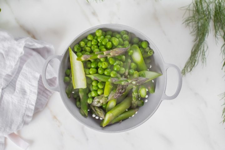 Peas and sliced asparagus in a colander after steaming
