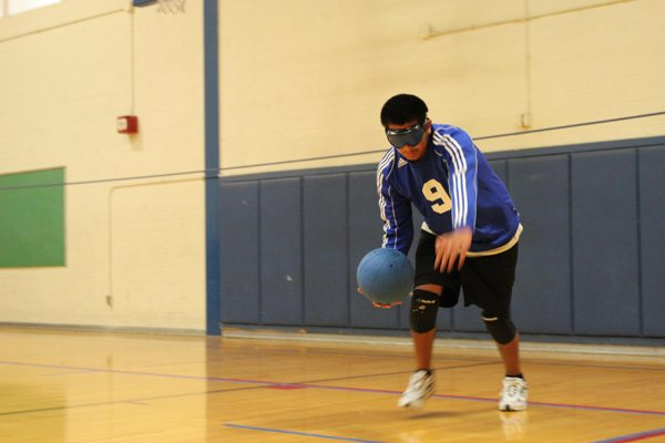 An ASB HS student playing Goalball is holding a Goalball at knee height and he appears ready to throw it during a game.