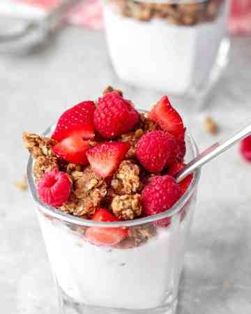 Overhear shot of a glass with a cherry yogurt, walnut granola and raspberries and strawberries.