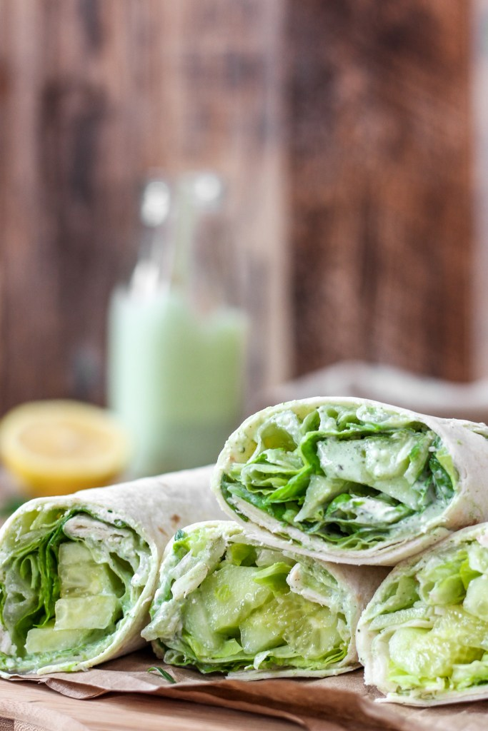 Cucumber Wraps with Green Goddess Dressing on a wood surface with brown paper.