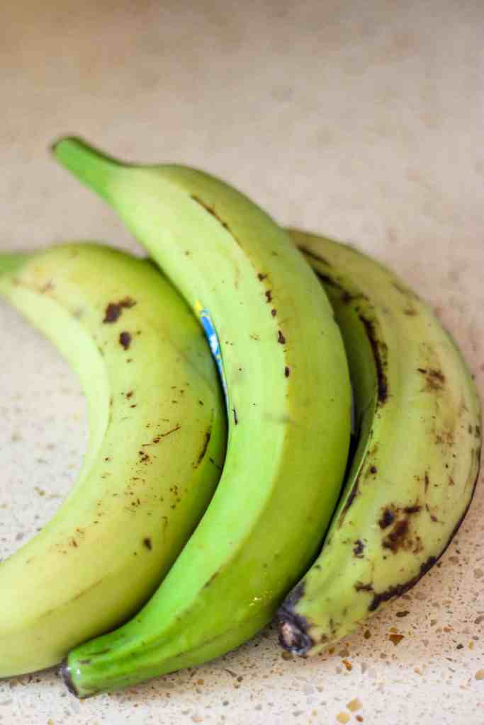 Three green plantains on a beige granite counter.