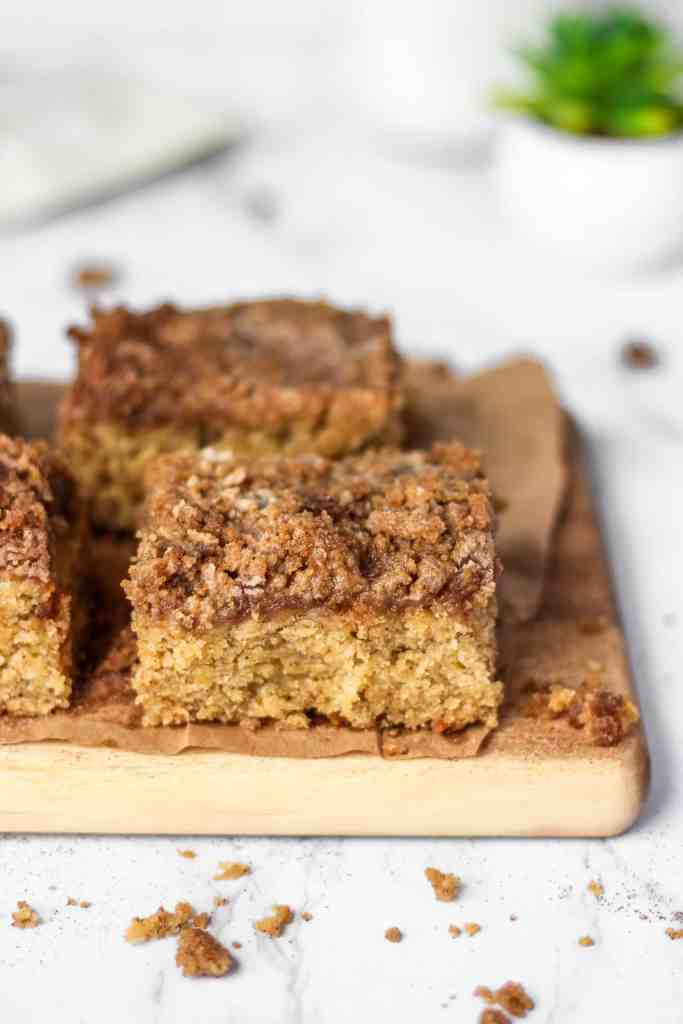 Banana coffee cake on a wood board with brown bag paper, crumbs, and a succulent in the back.