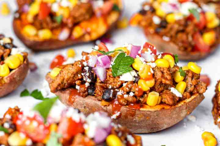 Close shot of the potatoes topped with corn, red onions, and parsley.