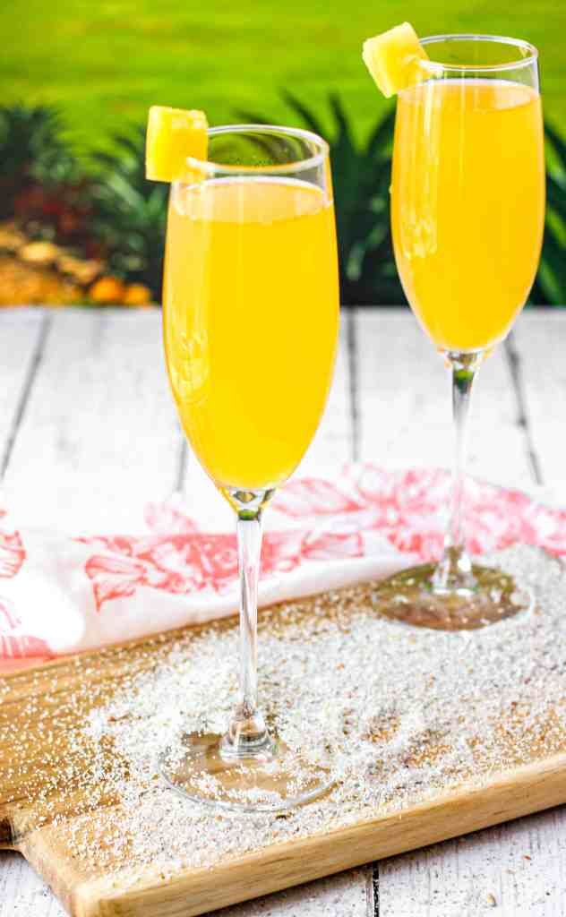 Two peach mimosas on a wood board with sand and a green background with low palm bushes.