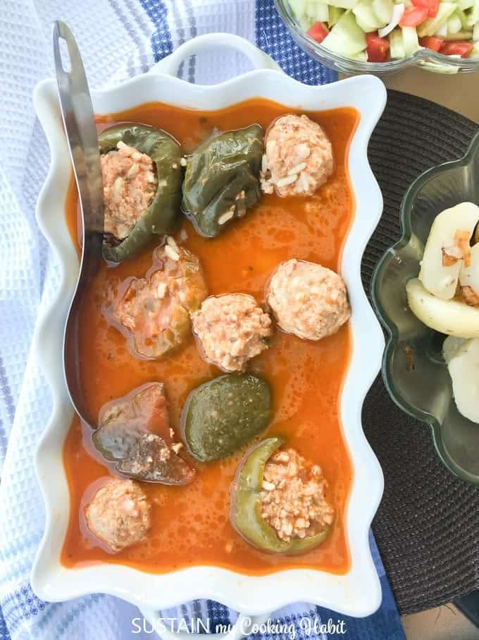 overhead shot of the stuffed peppers in sauce in a white casserole dish.