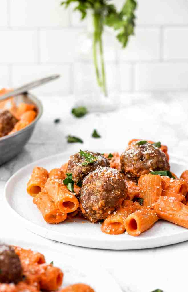 meatballs on rigatoni with vodka sauce on a white plate