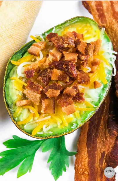 overhead shot of an egg stuffed avocado with cheese and bacon.